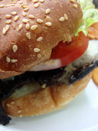 close up of  on white plate portabella mushroom burger with lettuce tomato and seseme bun Stock Photo