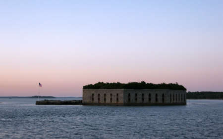 Historic Fort Gorges with American Flag waving at dusk in the harbor of Portland Maine.