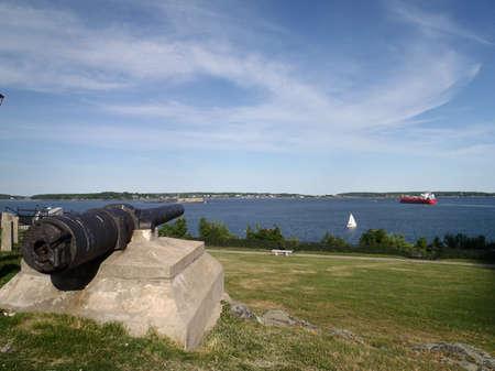 artillery shell: Ca��n recuperado de la USS Maine, hundido en el puerto de la Habana, Cuba el 15 de febrero de 1898 en Mostrar Fort Allen Park con barcos de vela y un petrolero navegando en la distancia en Portland, Maine