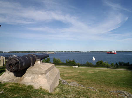 Gun recovered from the U.S.S. Maine, sunk in the Harbor of Havana, Cuba February 15th 1898 on display Fort Allen Park with Sail Boat and a oil tanker sailing in the distance in Portland, Maine