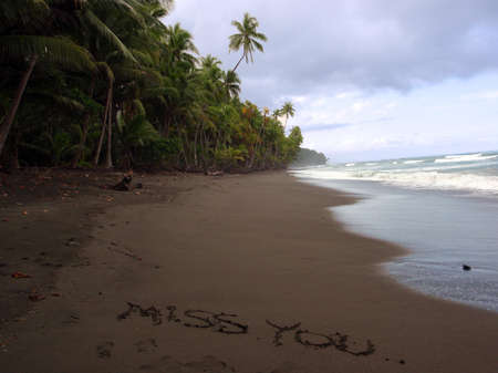 message: Miss You written in the sand on a remote beach in Punta Banco, Costa Rica on the Pacific Coast