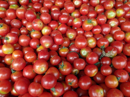 Organically grown red cherry tomatoes background on display at a farmers market photo