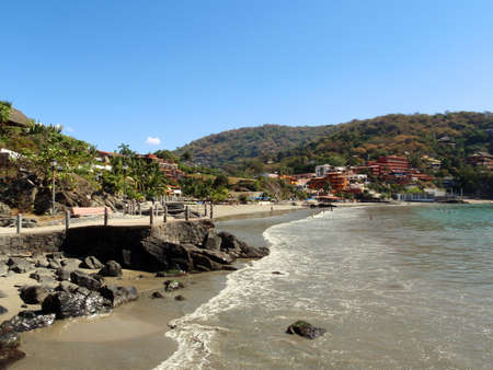 people play in the calm waves on a clear day at Playa La Ropa Beach in Zihuatanejo Mexico Stock Photo