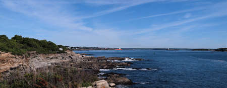 Panoramic of Portland Maine harbor area with rocky coastline in view
