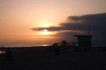 two Venice beach Lifeguard towers, beach truck, and people silhouettes at sunset in California. photo
