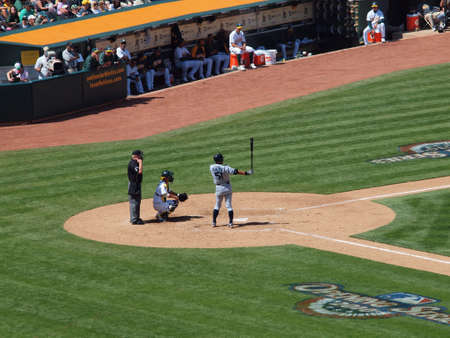 Ichiro Suzuki, Seattle Mariners does hes ritual pre-batting stance with catcher kurt suzuki and umpire waiting for the play to begin.  Athletics past Mariners 6-2: At Oakland coliseum, California April 9, 2010.