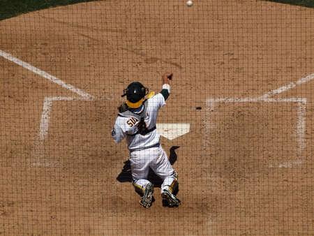 llegar tarde: Rojos 3 vs as 0: como Catcher Kurt Suzuki inicia nuevamente el balón para el lanzador durante el lanzamiento de calentamiento de cambio en las entradas finales de un juego. Puntos de sutura Ball pueden verse como el balón abandona su mano. Adoptada el 23 de junio de 2010 en el Coliseo de Oakland California