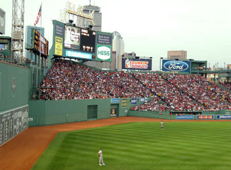 outfielders: Red Sox vs Athletics: As outfielders stand in front of the Green Monster at Fenway with crowded bleachers. taken June 2, 2010 Fenway Park Boston, Massachusetts.