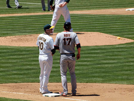 Giants 0 Vs. Athletics 3: Giants runner Aubrey Huff stands at first with As 1st baseman Daric Barton with pitcher holding the ball in the distance.  Taken May 23 2010 at the Coliseum Oakland California. Editorial