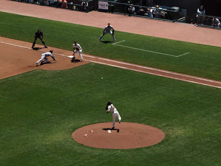 orioles: Giants Vs. Orioles: Giants two time Cy Young award winner Tim Lincecumthrows over to 1st base as runner slides back during a day game.  June 16 2010 Att Park San Francisco California