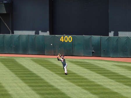 Bay Bridge Series: Giants Aaron Rowand catching a fly ball in center field by the 400 marker. May 23, 2010 The Oakland Coliseum featuring Baseball players and fans.
