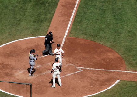 baseman: Giants vs. Pirates: San Francisco Giant Aaron Rowand celebrates a home run at homeplate taken at At&T Park San Francisco California on April 14, 2010.