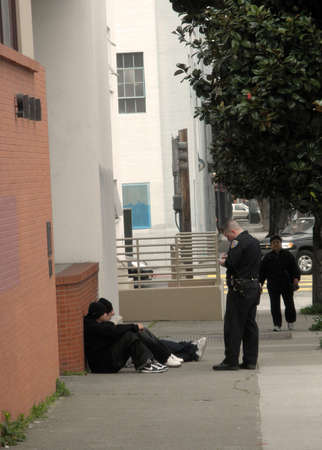 bystanders: San Francisco Police officer writes up street kids in the mission Febuary 1 2010 San Francisco California