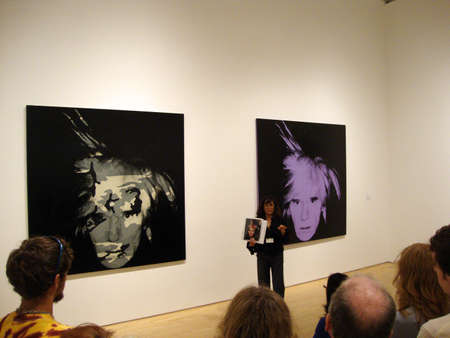 San Francisco MOMA docent speaks about Andy Warhol self portrait from the world famous Fisher Collection (founders of the GAP company).  Taken July 2, 2010 at the San Francisco Musuem of Modern Art in California