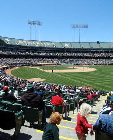 gradas estadio: Los fans toman en un juego desde la primera l�nea de base en un hermoso d�a durante la temporada de 2008 en el estadio de A. 04062008 El Coliseo de Oakland con jugadores de b�isbol y aficionados.  Editorial