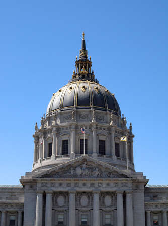 San Francisco City Hall with flags waving and dome reflecting the sun on a clear day. photo