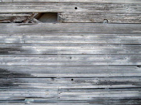adds: worns and tattered unpainted wood siding by the water which adds to its aged look