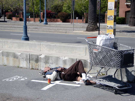 Homeless man sleeps on his shoes along the Embarcadero in San Francisco California, April 15, 2009