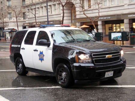 Ford Explorer SFPD cop vehicle rolls down market street during a Protest for House Keys, not handcuff on rainy day.  Taken January 20, 2010 San Francisco California.