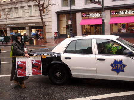 unrest: Protester holds House Keys, not handcuff sign in front of SFPD car on rainy day during a march down Market Street.  Taken January 20, 2010 San Francisco California. Editorial