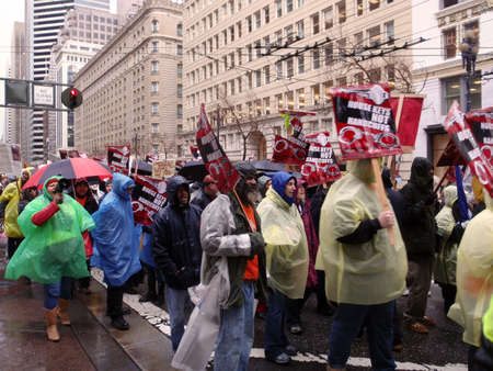 demonstrators: Protester holds House Keys, not handcuff sign  as they march down market street on rainy day.  Taken January 20, 2010 San Francisco California.