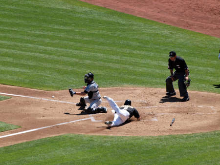Blue Jays vs. Athletics: Athletics Cliff Pennington slides head first into home as Blue Jays catcher waits for incoming ball.  Taken on August 18 2010 at Coliseum in Oakland California.