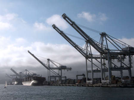 Shipping Cargo Boats line up in harbor under giants unloading cranes in Oakland Harbor with small sail boat passing by.  Taken August 4, 2010 Oakland California.