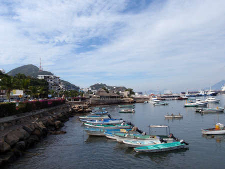 Small boats rest in the harbor of Manzanillo, Mexico with dramatic cloud scape.