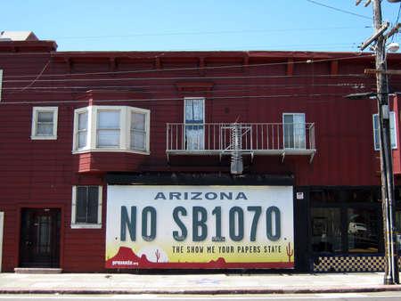 Arizona - The Show Me Your Papers State, license plate Ad from Presente.org on the side of a red building in the Mission, San Francisco.  Taken August 22, 2010, San Francisco.