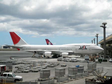 thier: JAL and Hawaiian Airlines planes sit at Honolulu International airport waiting to load up with passangers and cargo for thier next flight.  Taken September 3, 2010 Honolulu, Hawaii.
