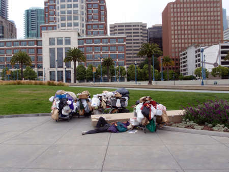 Homeless man sleeps with 4 shopping carts surrounding him along the Embarcadero with the GAP headquarters in the background in San Francisco California, June 16, 2009