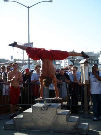 circus performers: SAN FRANCISCO - OCTOBER 11: British Circus performers put on a show at San Francisco Fishermans Wharf. Man does handstand splits while balancing on a board on a roller pin taken October 11 2010 San Francisco.