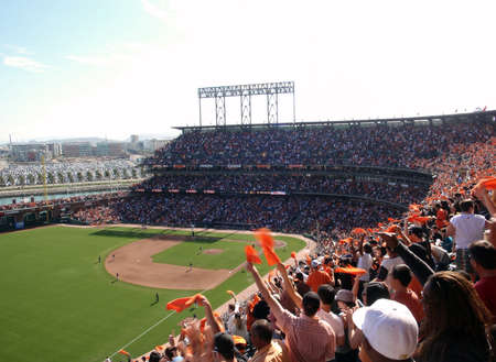 baseball stadium: Padres vs. Giants: Fans wave orange towels to celebrate giants hit on offense.  taken on October 2 2010 at Att Park in San Francisco California.