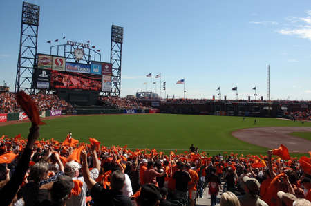Padres vs. Giants: Fans wave orange towels to pump up team before the start of the game as the big screen tells to do.  taken on October 2 2010 at Att Park in San Francisco California.