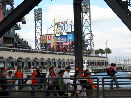 Padres vs. Giants: Giants Celebrate in Club house on big screen as fans celebrate the clinging of the Division Pennant. People walking away on third street bridge.  taken on October 3 2010 at Att Park in San Francisco California. Editorial