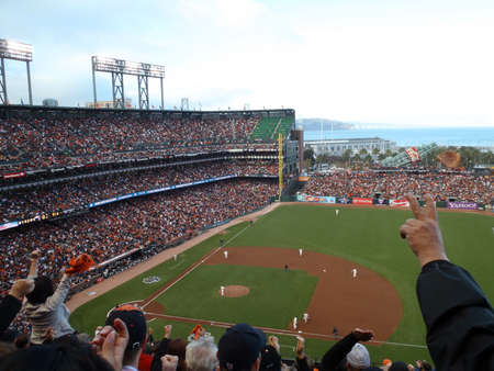 SAN FRANCISCO, CA - OCTOBER 20: San Francisco Giants vs. Philadelphia Phillies: Giants fans cheer for inning ending strikeout by Madison Bumgarner, one fan holds up peace sign as others wave rally rags, game four of the NLCS 2010 taken October 20, 2010 AT