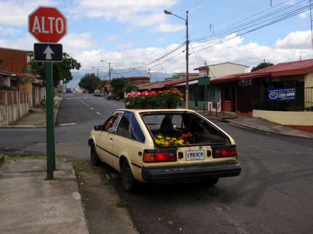 delievery: HEREDIA, COSTA RICA- AUGUST 11: Costa Rican Flower Delievery car at stop sign with flowers in back and on roof August 11, 2009 Heredia, Costa Rica.