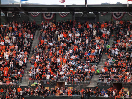 baseball crowd: SAN FRANCISCO, CA - OCTOBER 28: Giants fans in the upperdeck stand and cheer at the sell out event of game 2 of the 2010 World Series game between Giants and Rangers Oct. 28, 2010 AT&T Park San Francisco, CA.