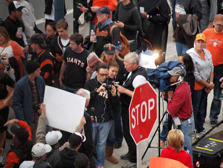 SAN FRANCISCO, CA - OCTOBER 28: TV Reporter does live report as fans gather around and one hold sign behind him game 2 of the 2010 World Series game between Giants and Rangers Oct. 28, 2010 AT&T Park San Francisco, CA.