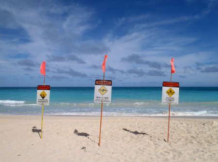 HONOLULU, HI - NOVEMBER 30: three Lifeguard warnings signs place in the sand on the beach warning of Dangerous Shorebreak, Man-O-War, and Strong currents taken November 30, 2010 on Waimanalo Beach on Oahu, Hawaii.