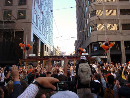 SAN FRANCISCO, CA - NOVEMBER 3: Giants fans celebrate and take photos of the passing of trolleys featuring giants players Pat Burrell and Aubrey Huff during world championship parade with fans waving and taking photos Nov. 3, 2010 San Francisco, CA.