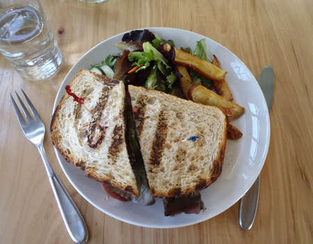 Overhead of Fancy Veggie Sandwich with side salad, fries, and glass of water. photo