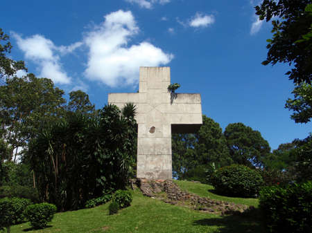 Large aged Cross surrounded by plants in Park in San Jose, Costa Rica