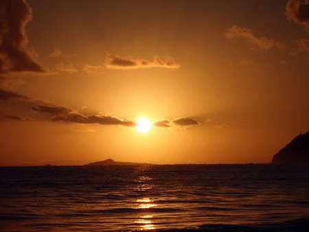 Sunrises over Kaohikaipu (BlackTurtle) Islands with the MakaPua lighthouse and Molokai visible in the distance. photo