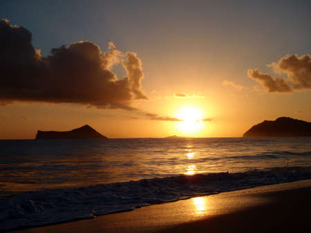 Sunrises over Kaohikaipu (BlackTurtle) Islands with the MakaPua lighthouse, Rabbit and Molokai Island visible in the distance. photo