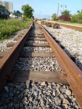 railtrack: Railroad tracks running into distance with through Portland, Maine with grass growing and rocks in between tracks. Stock Photo
