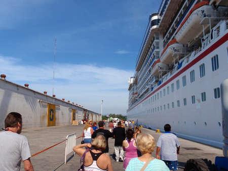 MANZANILLO, MEXICO - JANUARY 11: People Lining up to board Cruiseship at pier.  Taken January 11, 2010 Manzanillo, Mexico.
