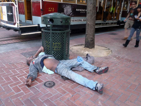 SAN FRANCISCO - AUGUST 24: Homeless man sleeps on ground resting against a trash can next to cable cars  San Francisco California, August 24, 2010