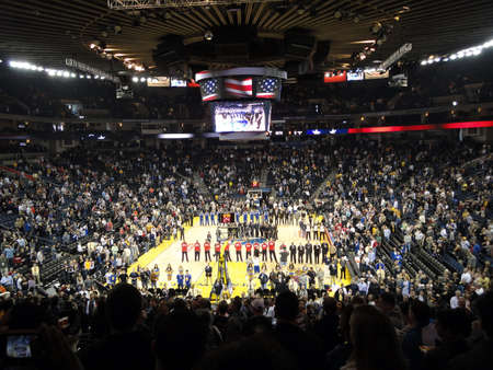 anthem: OAKLAND, CA - JANUARY 17: Nets vs. Warriors: Basketball Players and Oakland fans stand with hats removed during the national anthem. Taken January 17, 2011 Oracle Arena Oakland, CA.