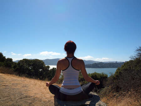 Attractive 20-something lady sits on tree stump and meditates on Angel Island in San Francisco Bay with the marin county visible in the distance.